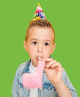 Small boy wearing birthday hat blowing into noisemaker